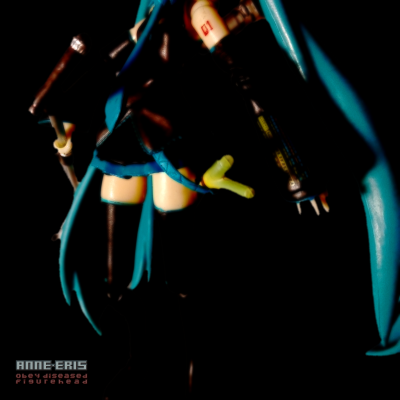Hatsune Miku doll holding a microphone stand, her head is cropped out of the image.